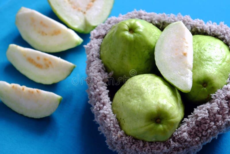 Φρούτα γκοϋαβών με τεμαχισμένος στο μπλε υπόβαθρο, πλούσια βιταμίνη C, ίνα και φτηνός στοκ εικόνες