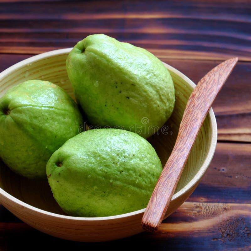 Φρούτα γκοϋαβών με τεμαχισμένος στο ξύλινο υπόβαθρο, πλούσια βιταμίνη C, ίνα και φτηνός στοκ εικόνα
