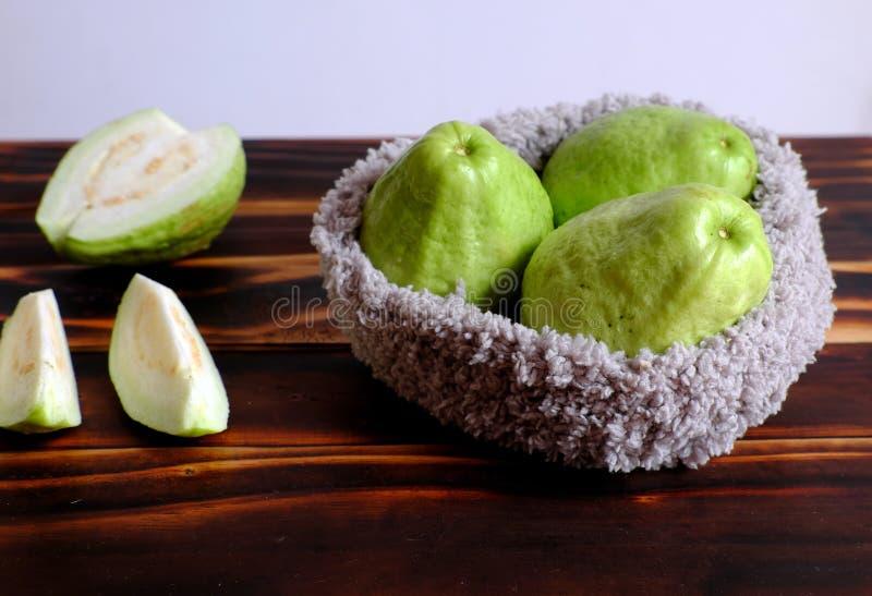 Φρούτα γκοϋαβών με τεμαχισμένος στο ξύλινο υπόβαθρο, πλούσια βιταμίνη C, ίνα και φτηνός στοκ φωτογραφία