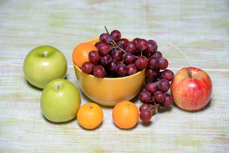 Φρούτα και κύπελλο στον ξύλινο πίνακα στοκ εικόνες