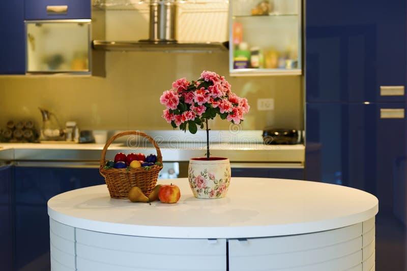 Φρούτα και λουλούδια στην μπλε εσωτερική κουζίνα στοκ φωτογραφία με δικαίωμα ελεύθερης χρήσης