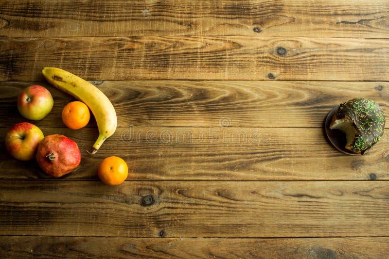 Φρούτα και doughnut με τη σοκολάτα σε ένα ξύλινο υπόβαθρο στοκ εικόνα με δικαίωμα ελεύθερης χρήσης
