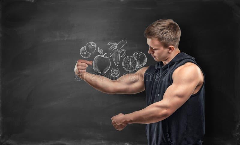 Φρούτα που απεικονίζονται στο μαύρο άτομο υποβάθρου και ικανότητας που παρουσιάζει bicep του κάτω από την εικόνα στοκ φωτογραφίες