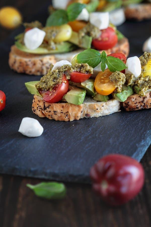 Φρυγανιά αβοκάντο με το τυρί και Pesto μοτσαρελών ντοματών βασιλικού στοκ φωτογραφία με δικαίωμα ελεύθερης χρήσης