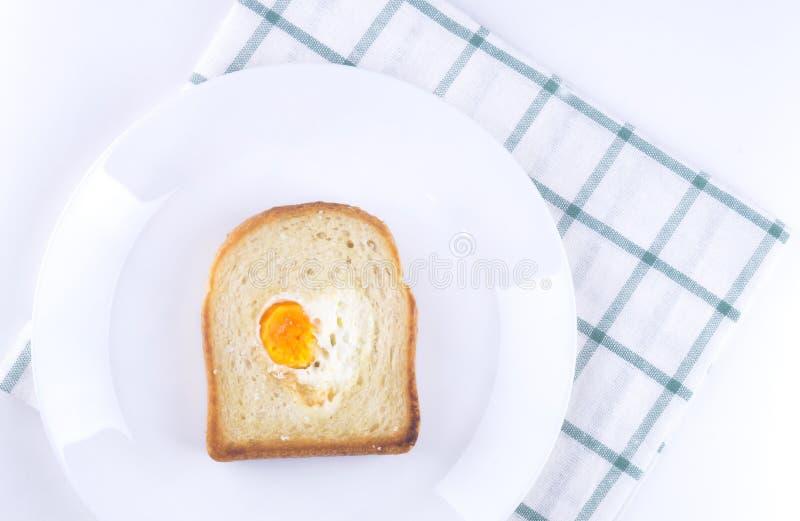 Φρυγανιά με τα ανακατωμένα αυγά σε μια μορφή καρδιών σε ένα άσπρο πιάτο στοκ εικόνες με δικαίωμα ελεύθερης χρήσης