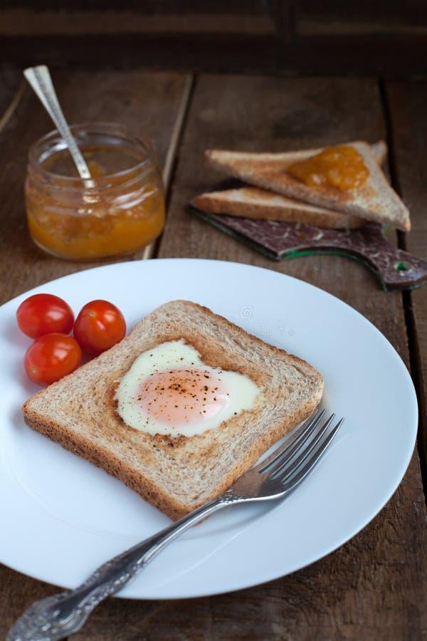 Φρυγανιά με το τηγανισμένο αυγό με μορφή των ντοματών καρδιών και κερασιών στοκ φωτογραφία