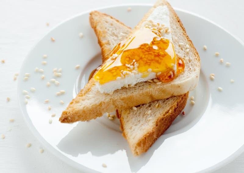 Φρυγανιά με το τυρί, το σουσάμι και το μέλι εξοχικών σπιτιών στοκ εικόνα