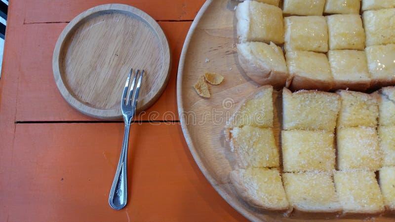 Φρυγανιά που ολοκληρώνεται με το καφετί βούτυρο στον πίνακα επάνω από τα πορτοκαλιά δέντρα στα ξύλινα πιάτα Και επισκευάζοντας μι στοκ εικόνα με δικαίωμα ελεύθερης χρήσης