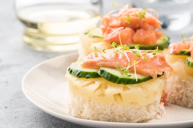 Φρυγανιά Bruschetta του άσπρου ψωμιού με τις φέτες των φρέσκων πράσινων νεαρών βλαστών σολομών ψαριών αγγουριών ανανά στοκ φωτογραφία με δικαίωμα ελεύθερης χρήσης