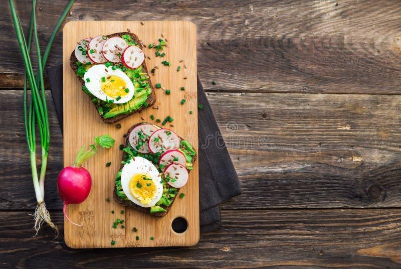 Φρυγανιές με το αβοκάντο, τα αυγά, το ραδίκι και το πράσινο κρεμμύδι στοκ φωτογραφία με δικαίωμα ελεύθερης χρήσης