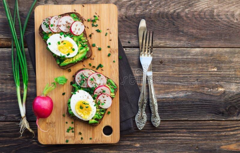 Φρυγανιές με το αβοκάντο, τα αυγά, το ραδίκι και το πράσινο κρεμμύδι στοκ εικόνες