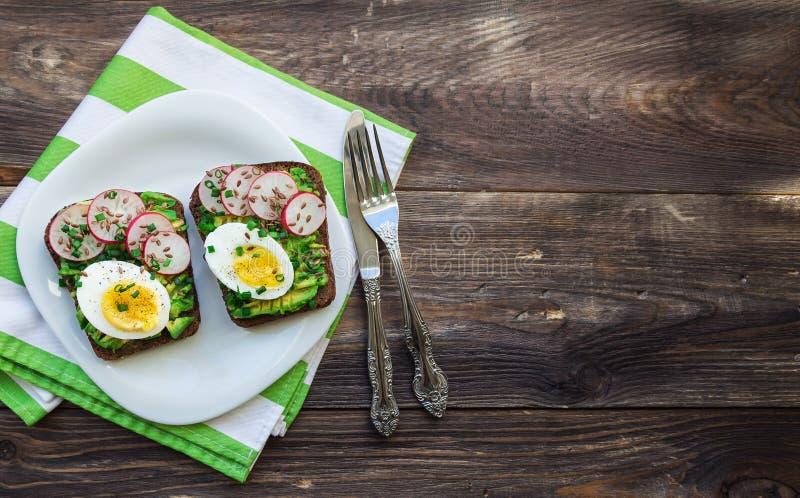 Φρυγανιές με το αβοκάντο, τα αυγά, το ραδίκι και το πράσινο κρεμμύδι στοκ εικόνα