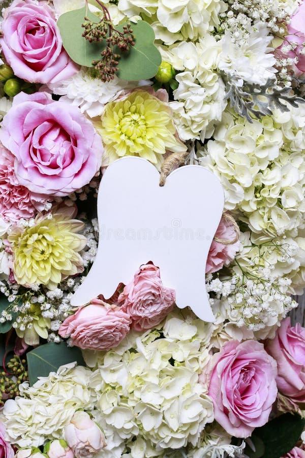 Φτερά αγγέλου μεταξύ των λουλουδιών Ρομαντική διακόσμηση λουλουδιών στοκ εικόνα με δικαίωμα ελεύθερης χρήσης