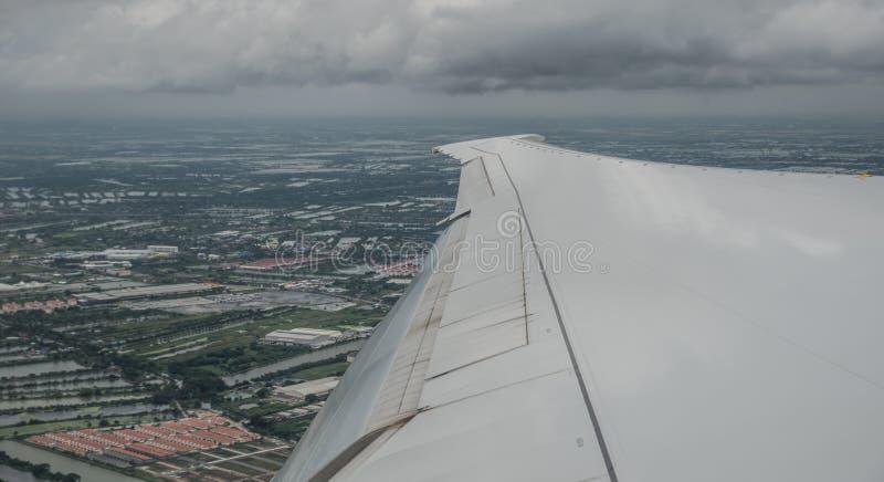 Φτερό ενός πετώντας αεροσκάφους με το υπόβαθρο εικονικής παράστασης πόλης στοκ φωτογραφία με δικαίωμα ελεύθερης χρήσης