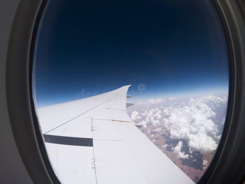 Φτερό και σύννεφα αεροπλάνων ` s πέρα από το έδαφος στοκ φωτογραφία με δικαίωμα ελεύθερης χρήσης