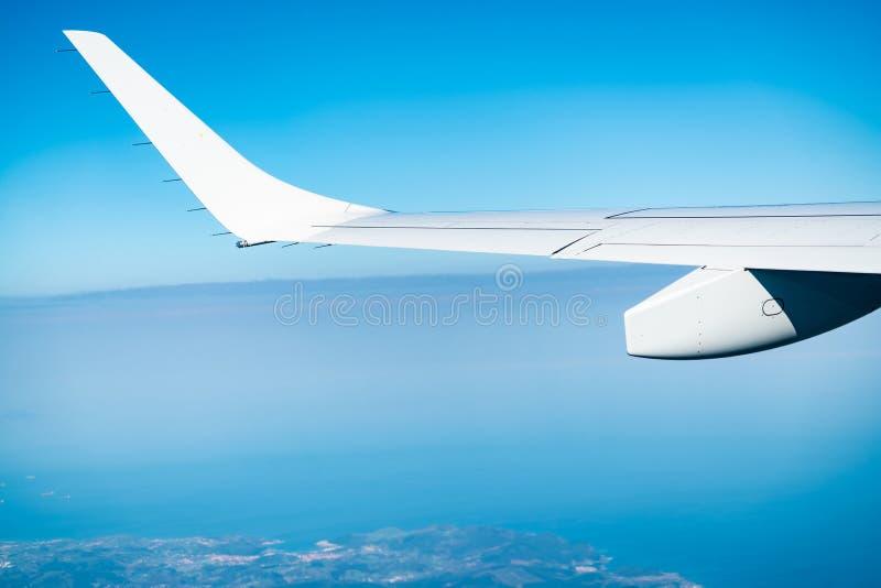Φτερό του αεροπλάνου πέρα από την πόλη και το έδαφος Αεροπλάνο που πετά στο μπλε ουρανό Φυσική άποψη από το παράθυρο αεροπλάνων Ε στοκ φωτογραφία με δικαίωμα ελεύθερης χρήσης