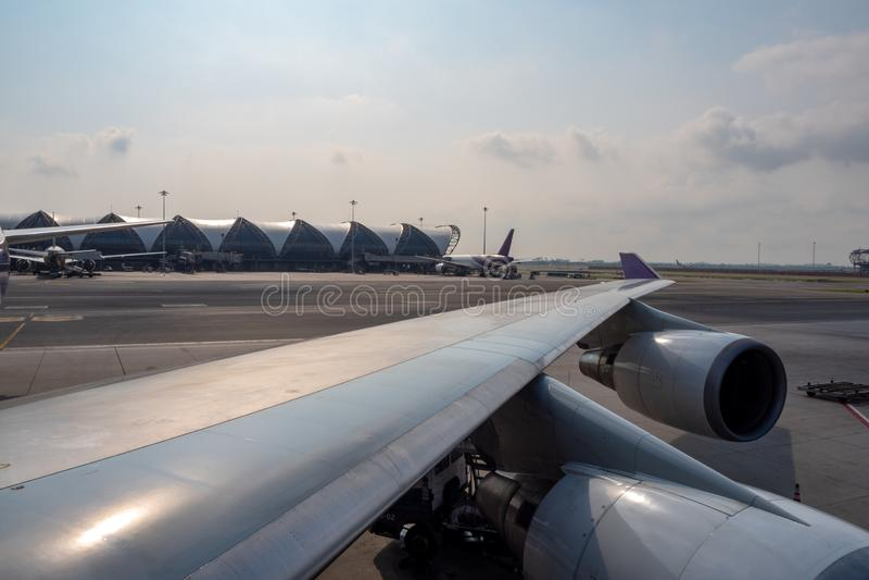 Φτερό του αεροπλάνου που σταθμεύουν στον αερολιμένα στο υπόβαθρο ουρανού σύννεφων στοκ φωτογραφία με δικαίωμα ελεύθερης χρήσης