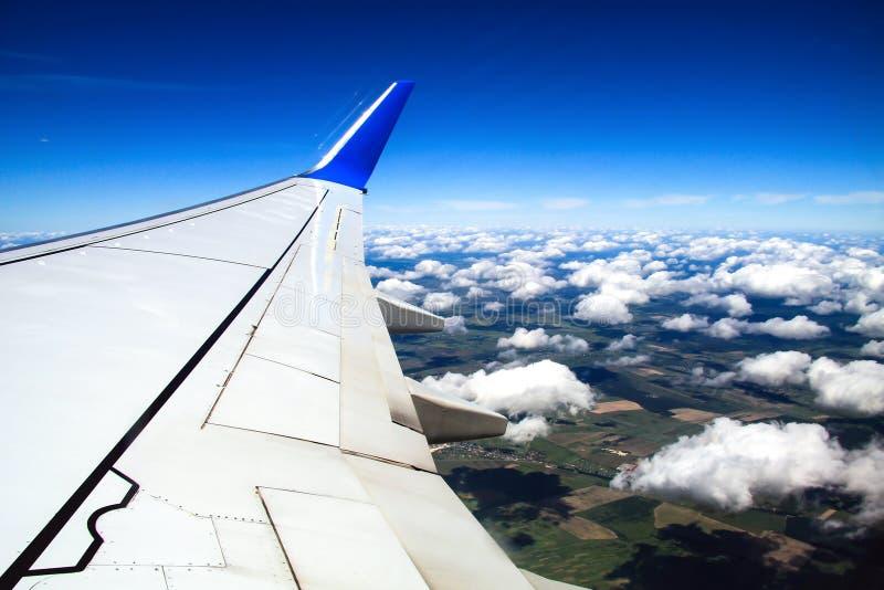 Φτερό του αεροπλάνου στο υπόβαθρο του μπλε ουρανού και των όμορφων σύννεφων Άποψη μέσω ενός παραθύρου αεροπλάνων στοκ φωτογραφία με δικαίωμα ελεύθερης χρήσης