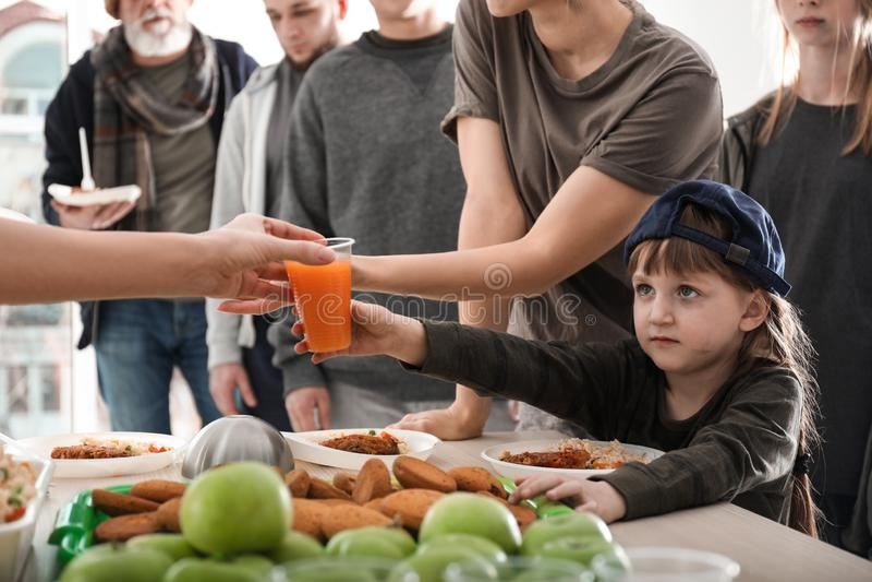 Φτωχοί άνθρωποι που λαμβάνουν τα τρόφιμα από τους εθελοντές στοκ εικόνες