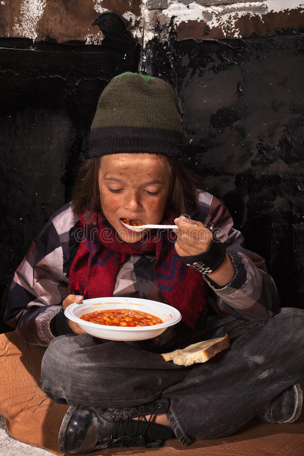 Φτωχό παιδί επαιτών που τρώει τα τρόφιμα φιλανθρωπίας στοκ εικόνες με δικαίωμα ελεύθερης χρήσης