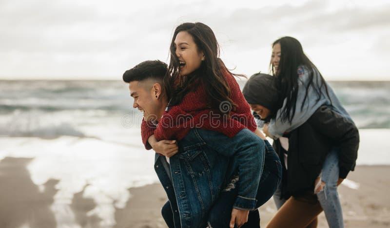 Φυλή σηκωήμαστε στην πλάτη στην παραλία στοκ εικόνα