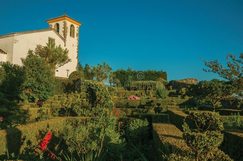 Φυλλώδεις άκρη και οι Μπους σε έναν πολύβλαστο ανθισμένο κήπο με την παλαιά εκκλησία στοκ φωτογραφίες