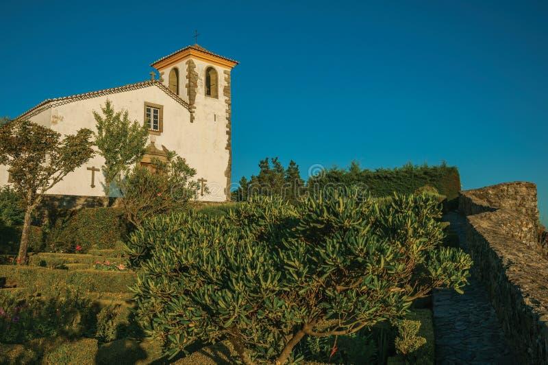 Φυλλώδεις άκρη και οι Μπους σε έναν πολύβλαστο ανθισμένο κήπο με την παλαιά εκκλησία στοκ φωτογραφία με δικαίωμα ελεύθερης χρήσης