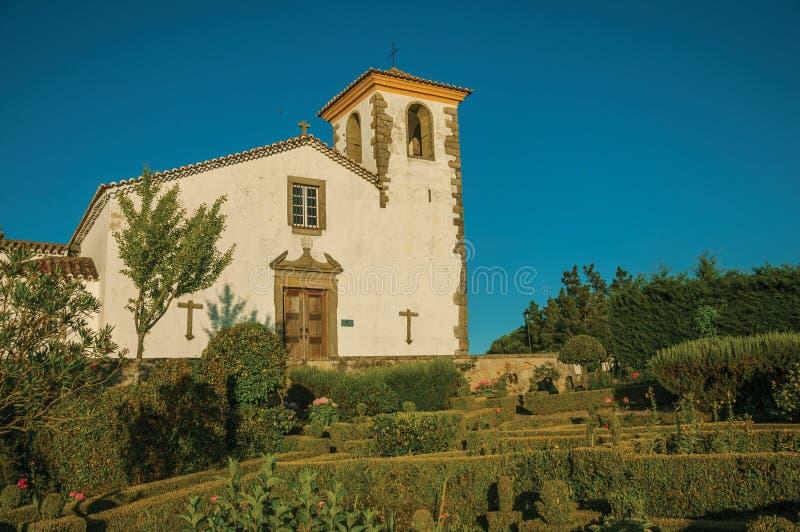Φυλλώδεις άκρη και οι Μπους σε έναν πολύβλαστο ανθισμένο κήπο με την παλαιά εκκλησία στοκ εικόνες