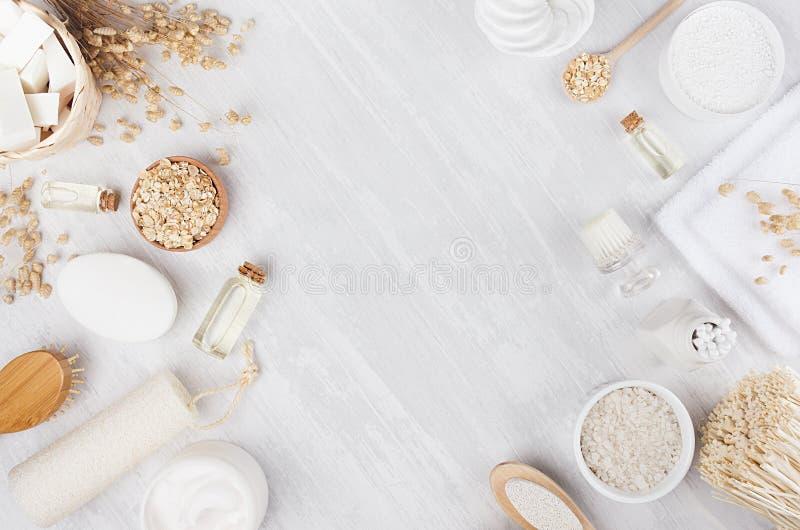 Φυσικά καλλυντικά βιοτεχνίας - τα άσπρα εξαρτήματα κρέμας, ελαίου, πετσετών και λουτρών στο μαλακό ελαφρύ άσπρο ξύλινο πίνακα, πλ στοκ εικόνες