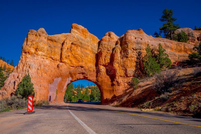 Φυσική άποψη της ζάλης της φυσικών γέφυρας κόκκινου ψαμμίτη και του δρόμου ασφάλτου στο εθνικό πάρκο φαραγγιών του Bryce στη Γιού στοκ φωτογραφία
