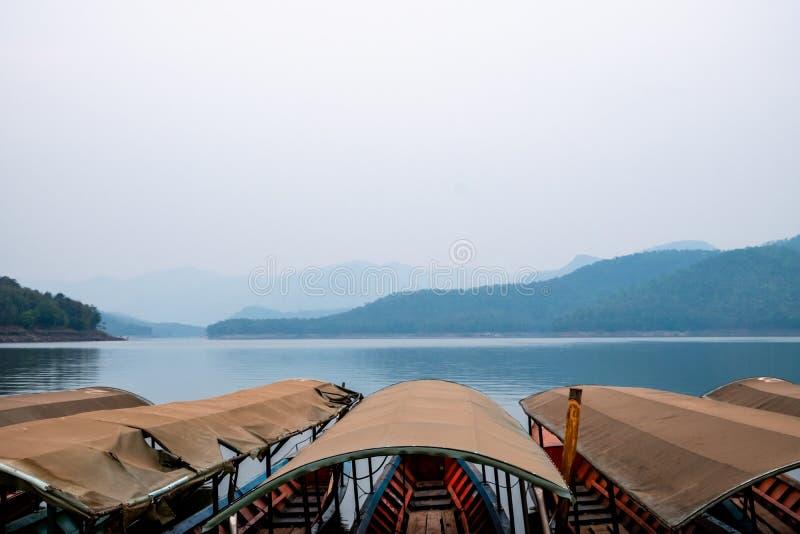 Φυσική άποψη της λίμνης με τα βουνά μια νεφελώδη ημέρα με τη σειρά των βαρκών μακρύς-ουρών που δένουν στο πρώτο πλάνο στοκ φωτογραφία