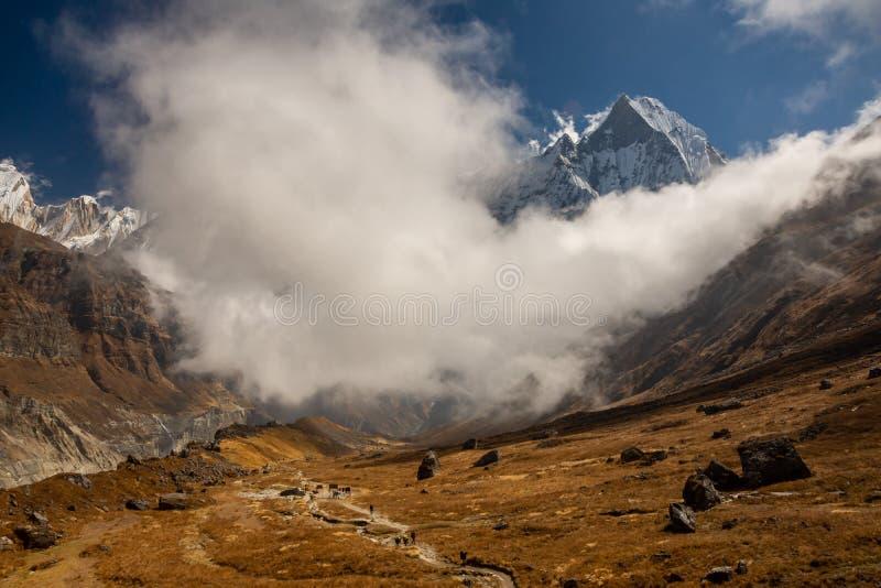 Φυσική άποψη της ουράς ψαριών Machapuchare που περιβάλλεται από τα σύννεφα και την πορεία στο στρατόπεδο βάσεων Annapurna, Ιμαλάι στοκ φωτογραφία με δικαίωμα ελεύθερης χρήσης