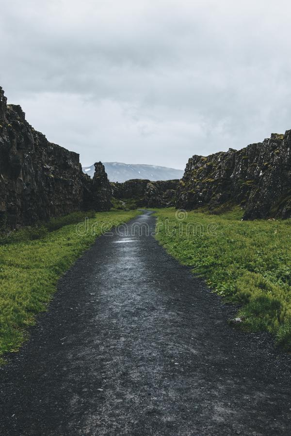 φυσική άποψη της πορείας στις ορεινές περιοχές κάτω από το νεφελώδη ουρανό στο εθνικό πάρκο Thingvellir στοκ εικόνες