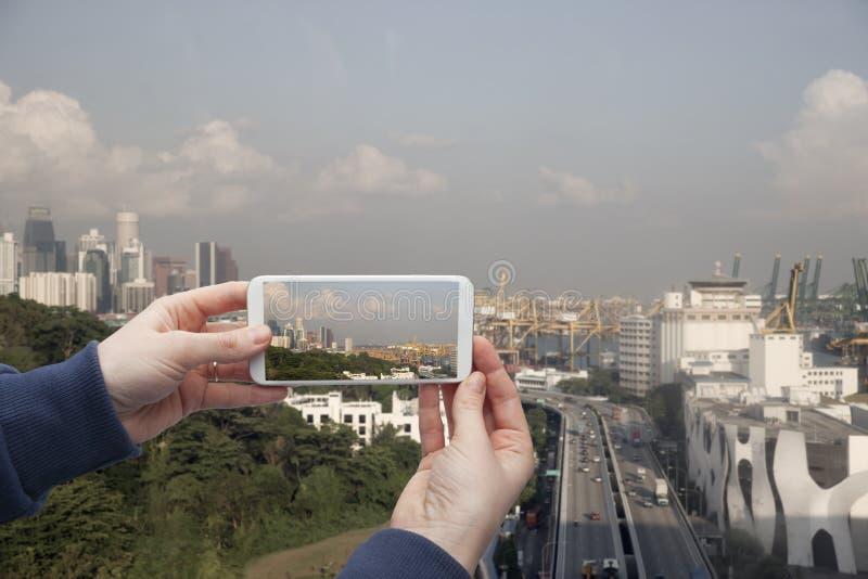 Φυσική άποψη του χεριού της Σιγκαπούρης με ένα smartphone, στην οθόνη του οποίου το αστικό τοπίο στοκ φωτογραφία με δικαίωμα ελεύθερης χρήσης