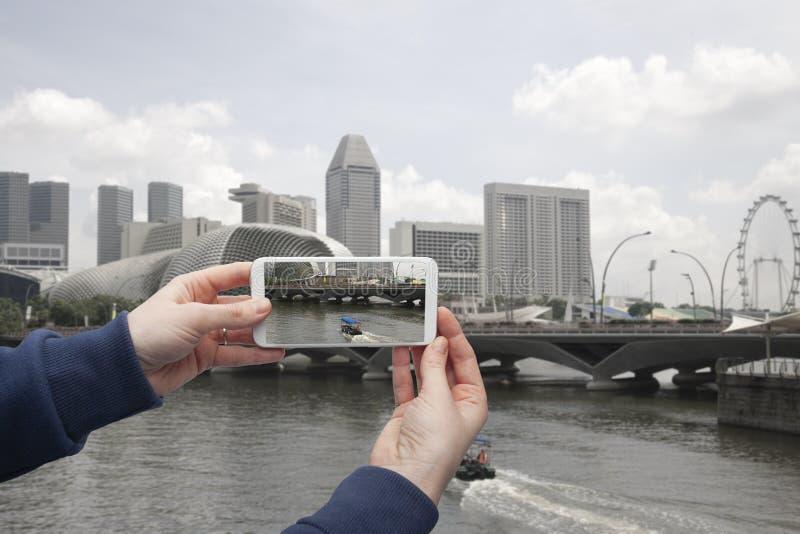 Φυσική άποψη του χεριού της Σιγκαπούρης με ένα smartphone, στην οθόνη του οποίου το αστικό τοπίο στοκ φωτογραφίες