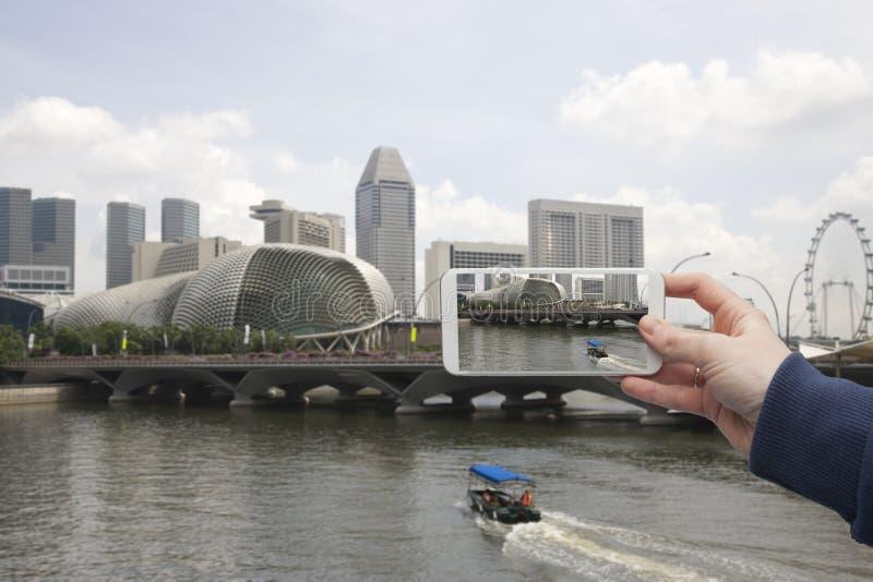 Φυσική άποψη του χεριού της Σιγκαπούρης με ένα smartphone, στην οθόνη του οποίου το αστικό τοπίο στοκ εικόνα με δικαίωμα ελεύθερης χρήσης