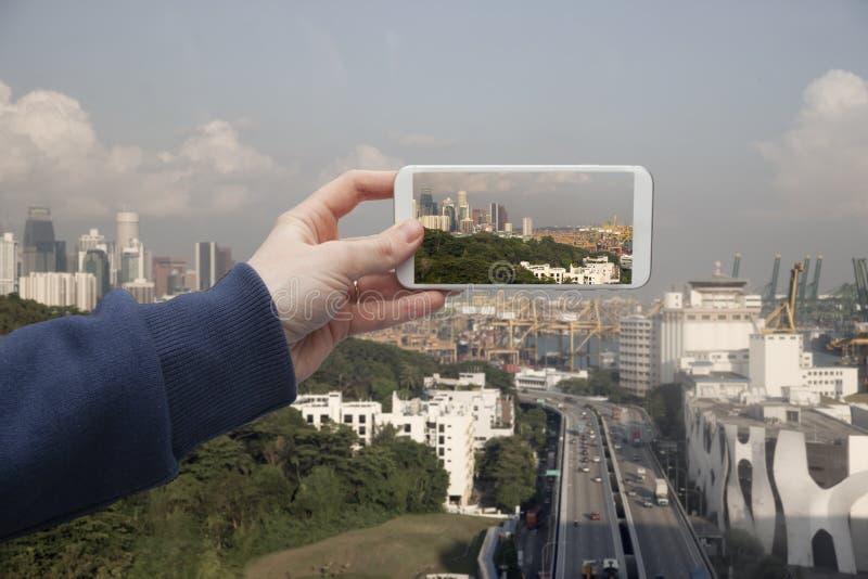 Φυσική άποψη του χεριού της Σιγκαπούρης με ένα smartphone, στην οθόνη του οποίου το αστικό τοπίο στοκ εικόνες με δικαίωμα ελεύθερης χρήσης