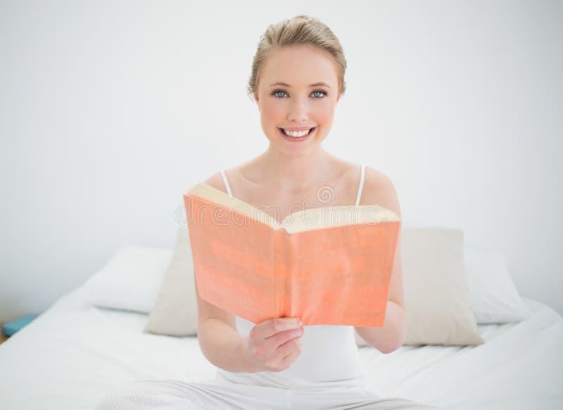 Φυσική ευτυχής ξανθή εκμετάλλευση ένα βιβλίο στοκ εικόνα με δικαίωμα ελεύθερης χρήσης