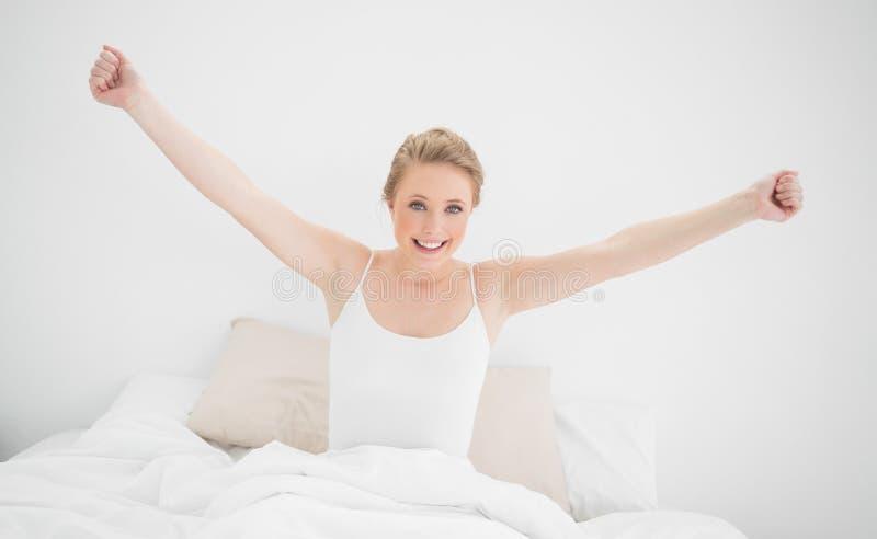 Φυσική ξανθή συνεδρίαση χαμόγελου στο κρεβάτι και τέντωμα των όπλων της στοκ εικόνες