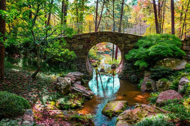 Φυσική στρογγυλή πέτρινη γέφυρα πέρα από ένα ρεύμα με την ανάδυση χρωμάτων πτώσης στοκ φωτογραφίες με δικαίωμα ελεύθερης χρήσης