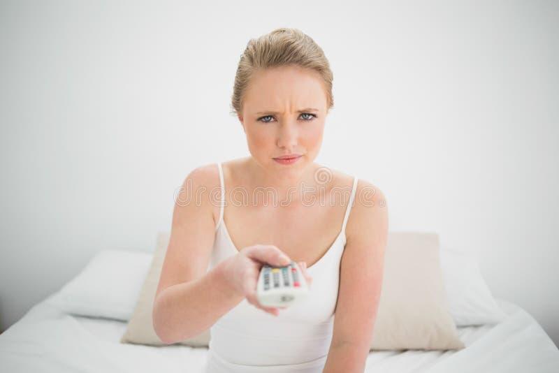 Φυσική συνοφρύή ξανθή εκμετάλλευση μακρινή καθμένος στο κρεβάτι στοκ φωτογραφία με δικαίωμα ελεύθερης χρήσης