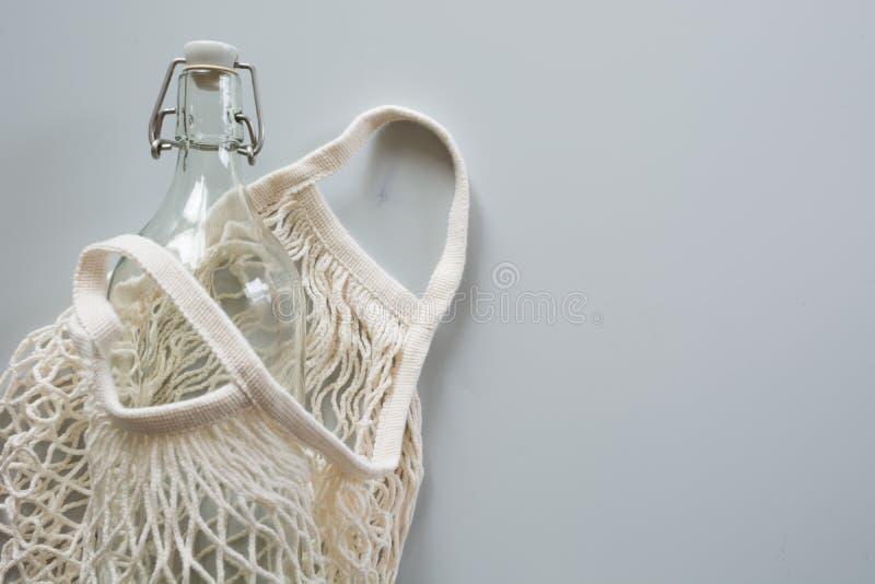 Φυσική υφαντική τσάντα πλέγματος Eco με το μπουκάλι μετάλλων και γυαλιού για την επαναχρησιμοποίηση Βιώσιμη έννοια τρόπου ζωής Μη στοκ φωτογραφίες