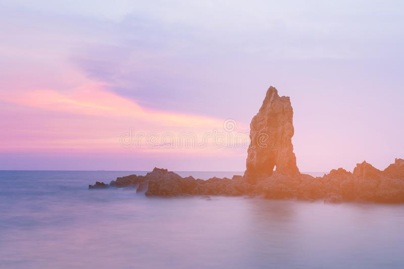 Φυσικός βράχος πέρα από τον ορίζοντα ακροθαλασσιών μετά από τον τόνο ηλιοβασιλέματος στοκ εικόνα