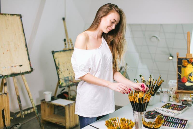 Φυσικός ζωγράφος δασκάλων ομορφιάς στο στούντιό της που προετοιμάζεται σε μια κατηγορία τέχνης στοκ εικόνα