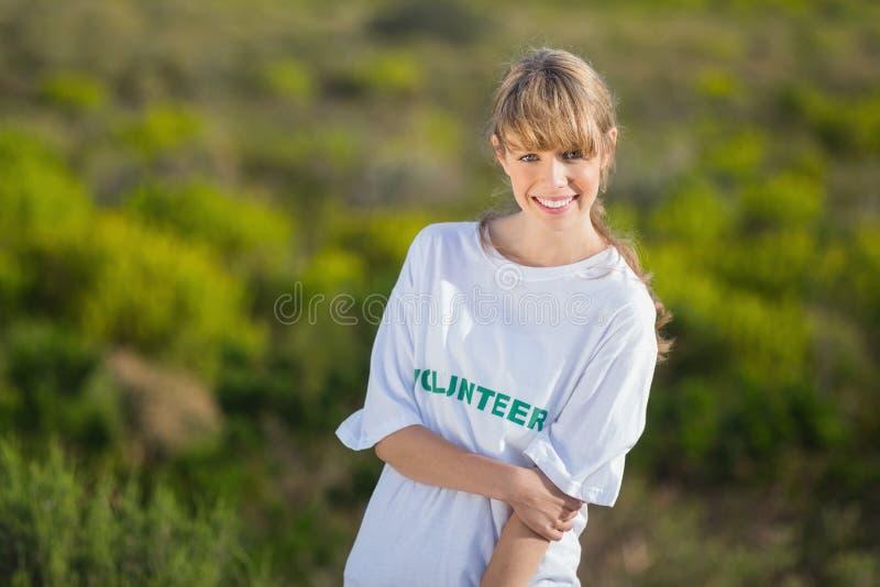 Φυσικός νέος ξανθός φορώντας μια να προσφερθεί εθελοντικά μπλούζα στοκ εικόνες