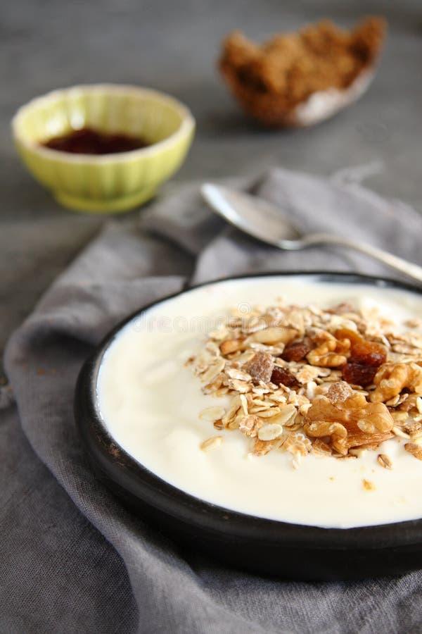 Φυσικό γιαούρτι με το muesli στο παλαιό γκρίζο κύπελλο στοκ φωτογραφίες