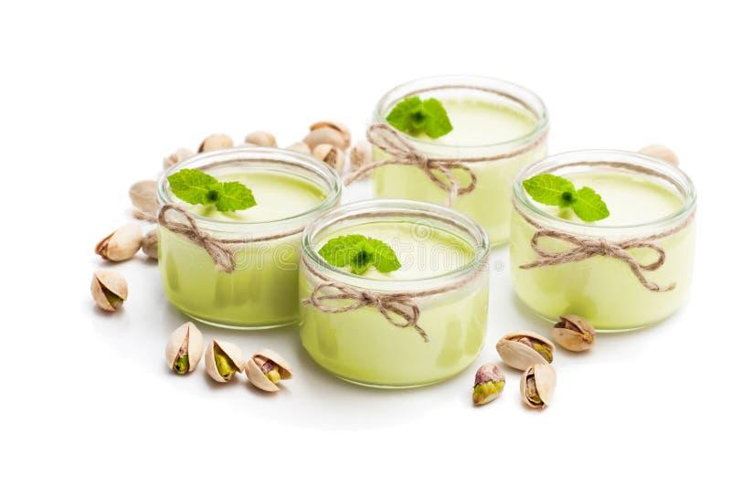 Φυσικό γιαούρτι φυστικιών σε ένα μικρό βάζο γυαλιού που απομονώνεται στο λευκό στοκ φωτογραφίες
