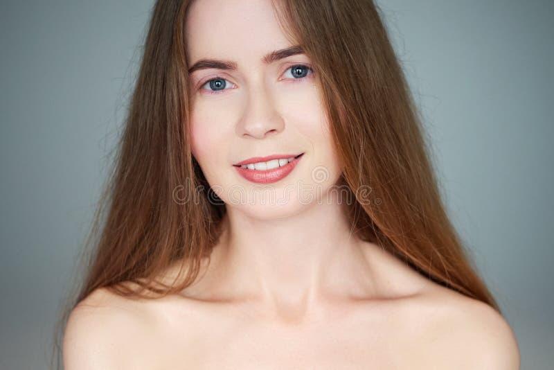 Φυσικό ελαφρύ στενό επάνω πορτρέτο ομορφιάς της όμορφης ξανθής γυναίκας με τους μακρυμάλλεις γυμνούς ώμους μπλε ματιών που εξετάζ στοκ εικόνες