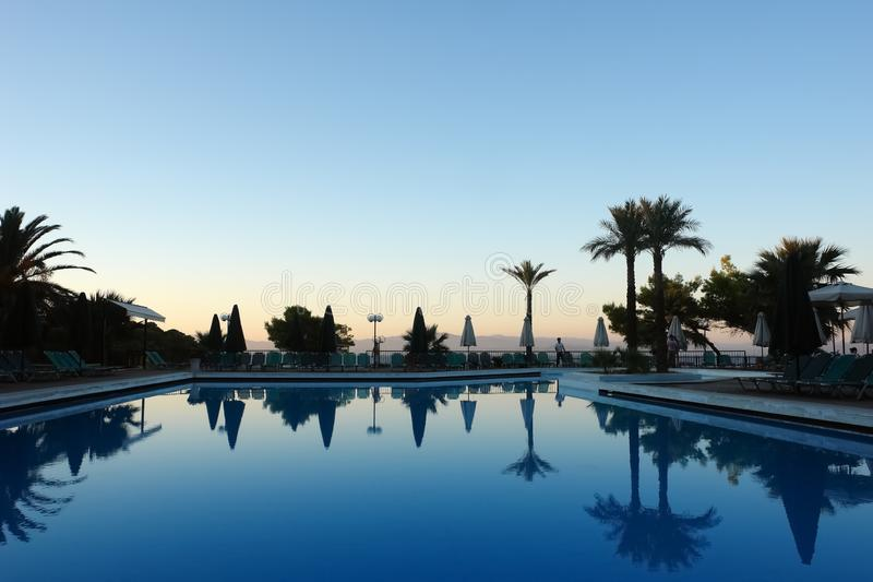 Φυσικό ηλιοβασίλεμα από τη θάλασσα, την μπλε λίμνη και τους φοίνικες σε ένα ξενοδοχείο μέσα στοκ φωτογραφία