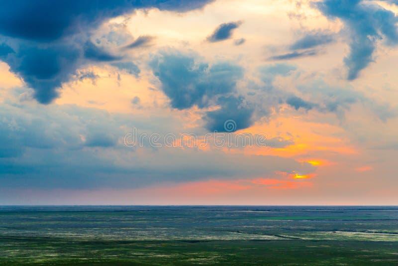 Φυσικό ηλιοβασίλεμα με τα σύννεφα στον ουρανό στη στέπα στοκ εικόνα